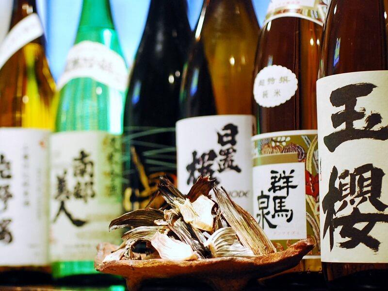 山盛りのひれが皿に山盛りに盛られています。数多く並ぶ日本酒の瓶の前に置かれたそのひれは、えいひれを代表に、そのまま食べても美味しいおつまみ。酒に入れて燗酒にして、ひれ酒を楽しんでみてはいかがでしょう。お店で飲むことを思い浮かべる方も多いかと思いますが、ご自宅でもかんたんにおいしいひれ酒を楽しむことができるんです。