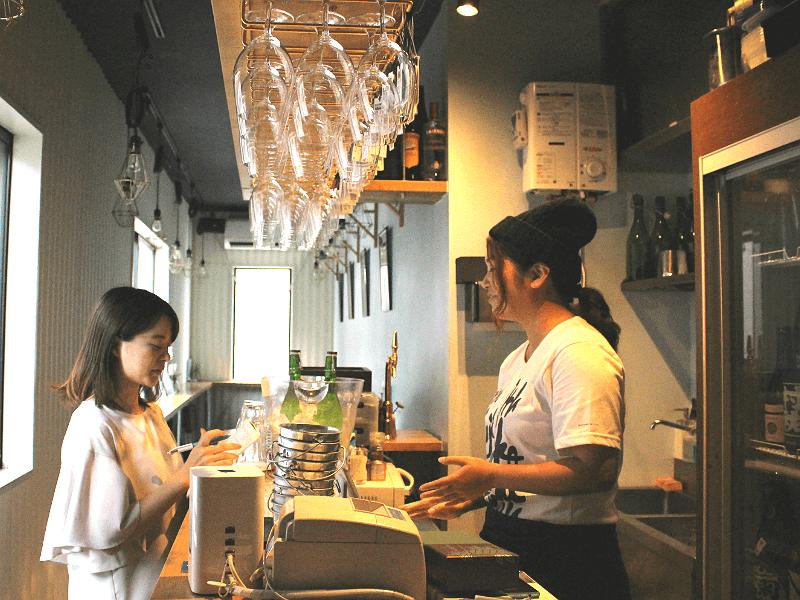 渋谷のSAKESTANDで若い女性が店員にインタビューをしている画像