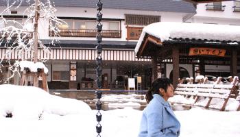 越後湯沢の冬景色のなか、女性が足湯に入っている写真