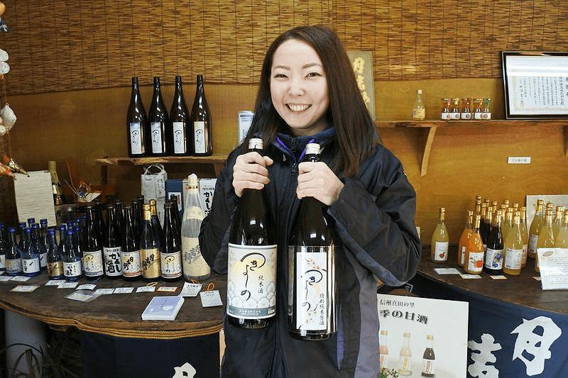 酒瓶を持ってにっこりほほ笑む長野県上田市・若林醸造の女性杜氏