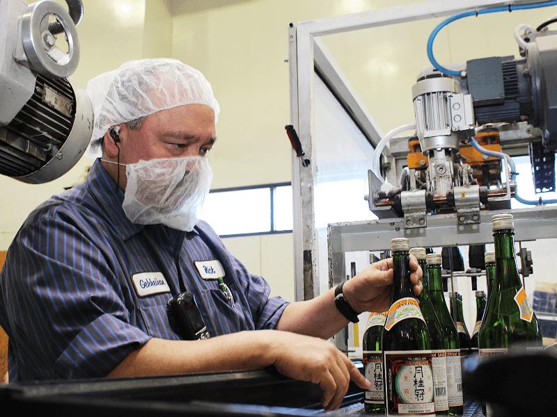 製造プロダクション・マネージャーのリックさんがボトル詰めラインで働く様子