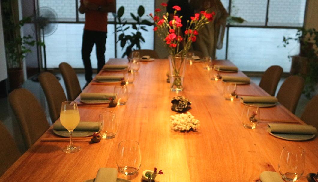 Cooking In Motionのクッキングアトリエ・La Nave de Sake/Sake Warehouseのテーブルにワイングラスと花が置いてある