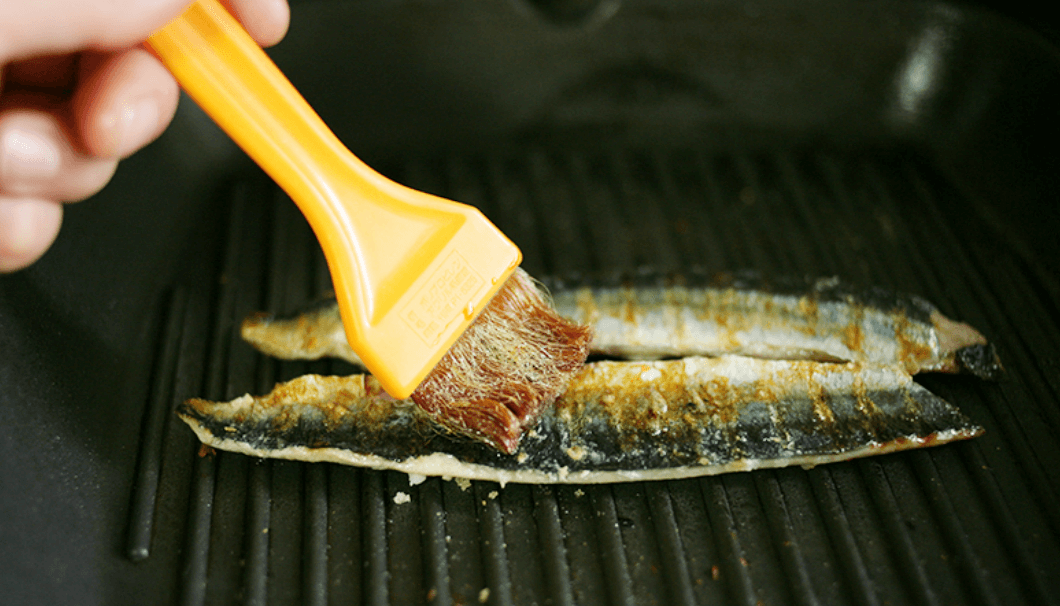 焼いている秋刀魚に醤油を塗っているところ