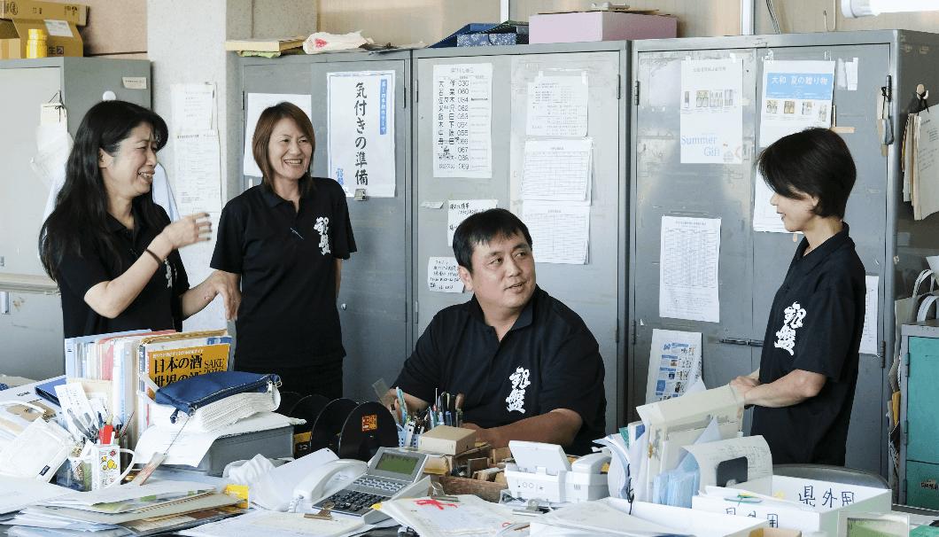 事務所で談笑する田中社長とスタッフの方々。
