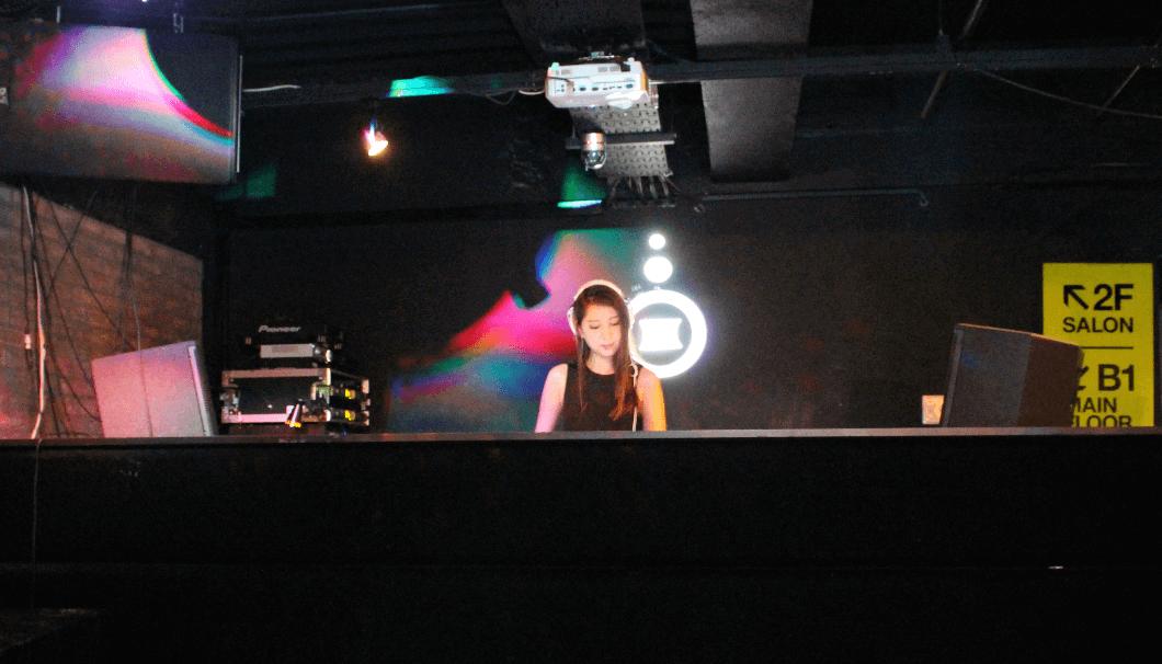 クラブで行われる日本酒イベントSAKENISTAのステージでDJする女性