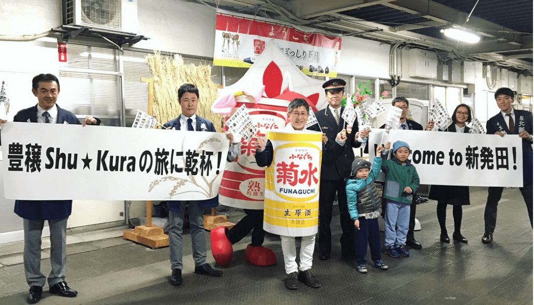 駅のホームで「ふなぐちくん」を自ら着て手を振る髙澤社長