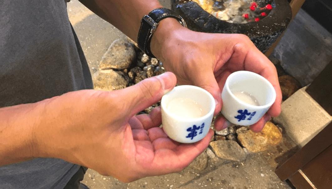 手におちょこを2つ持つ。原田酒造場では、200円でおちょこを買えば、冷蔵庫にある全ての日本酒を一杯ずつ飲める