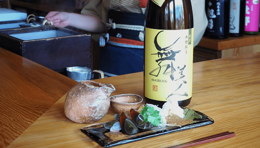 「自家製リコッタとピータンの胡麻山椒ダレ」と「舞美人 山廃純米酒」(美川酒造場/福井県)。