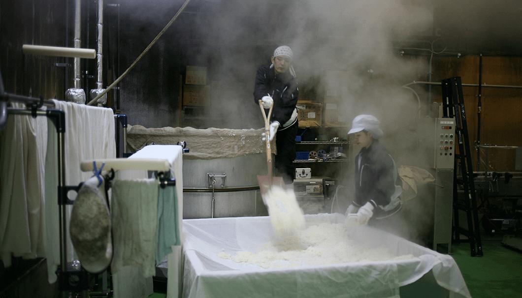蒸しあがったお米を移動式の台へ移しているところ