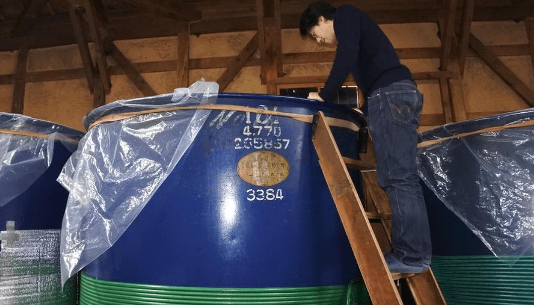 タンクの中を覗く白杉酒造の代表取締役、白杉悟さん