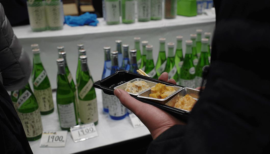 おつまみをもちながら日本酒を飲む写真