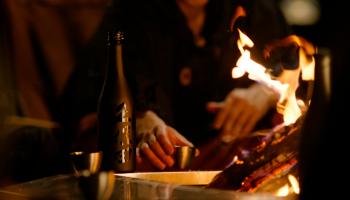 株式会社スノーピーク(新潟県三条市)と、朝日酒造株式会社(新潟県長岡市)が「アウトドアで日本酒を楽しむ。」という新しいカテゴリーの創出を目指して共同開発し、昨年9月に発売した「久保田 雪峰」のイメージ画像。火に向かいながら「久保田 雪峰」をかたわらに置く写真