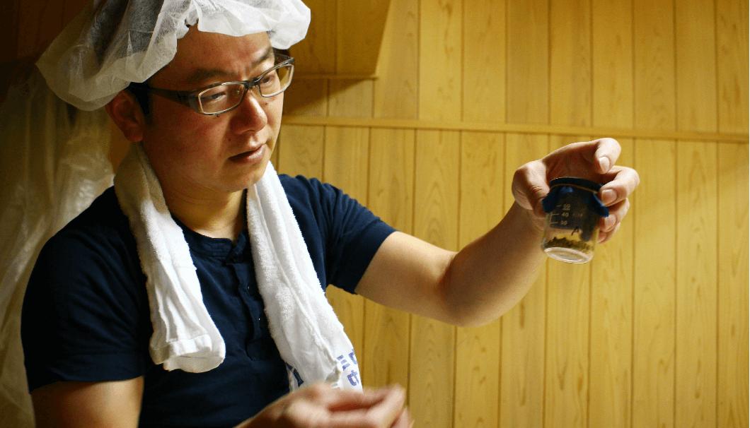 宏和日立酒造、麹室で種麹が入った瓶を持つ長岡杜氏