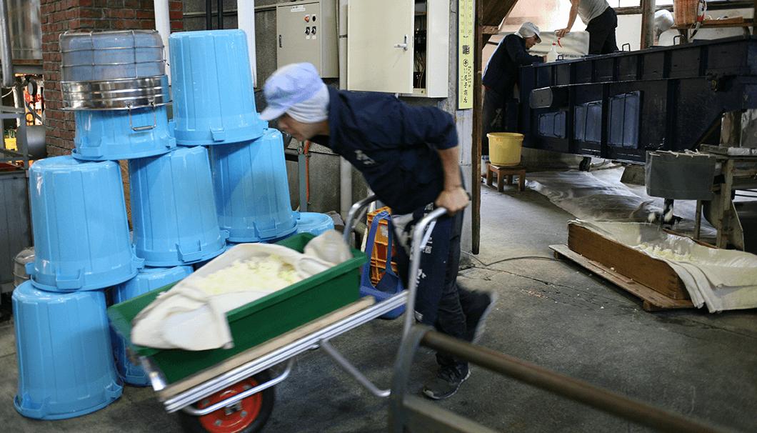 放冷機を通った掛米は一輪車で移動させる