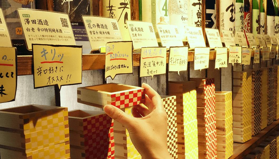 AKATSUKI NO KURA(あかつきのくら)の店内の壁一面に並んだ日本酒から飲みたいお酒の枡を一つ取り、日本酒カウンターへ向かう
