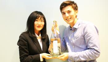 サイボウズ・「甲子春酒 香んばし」のボトルを持つ渡邊義さんと國弘遥さん