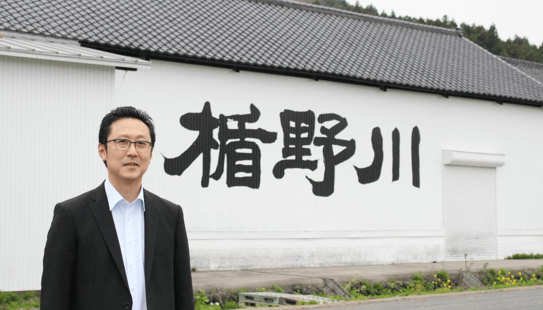 楯の川酒造をバックに取った佐藤社長の写真