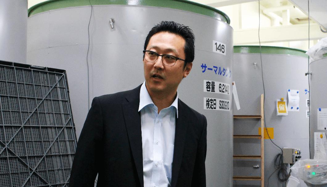日本酒のタンクをバックに佐藤社長が話している写真