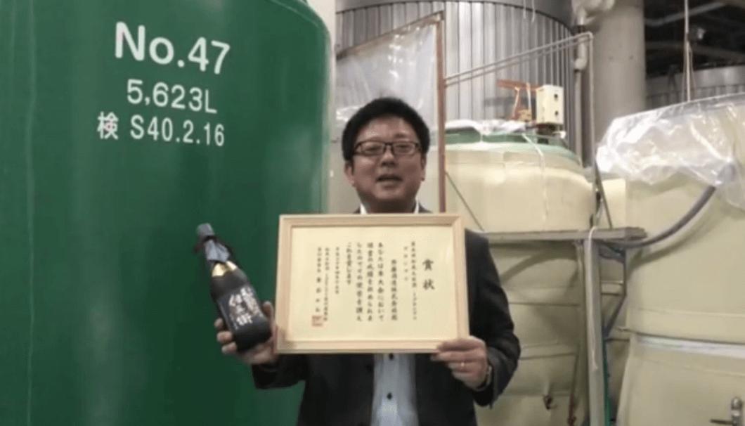 齊藤酒造の方がタンクの前でボトルと賞状を持って立っている写真