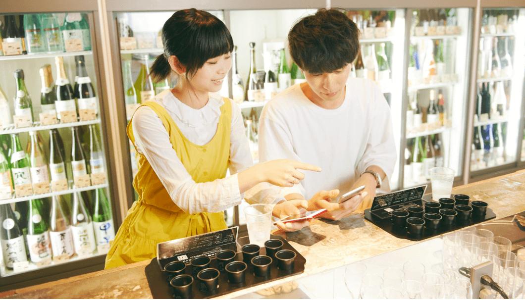 人工知能とブラインドテイスティングによる日本酒の味覚判定サービス「YUMMY SAKE」をしている男女の写真画像
