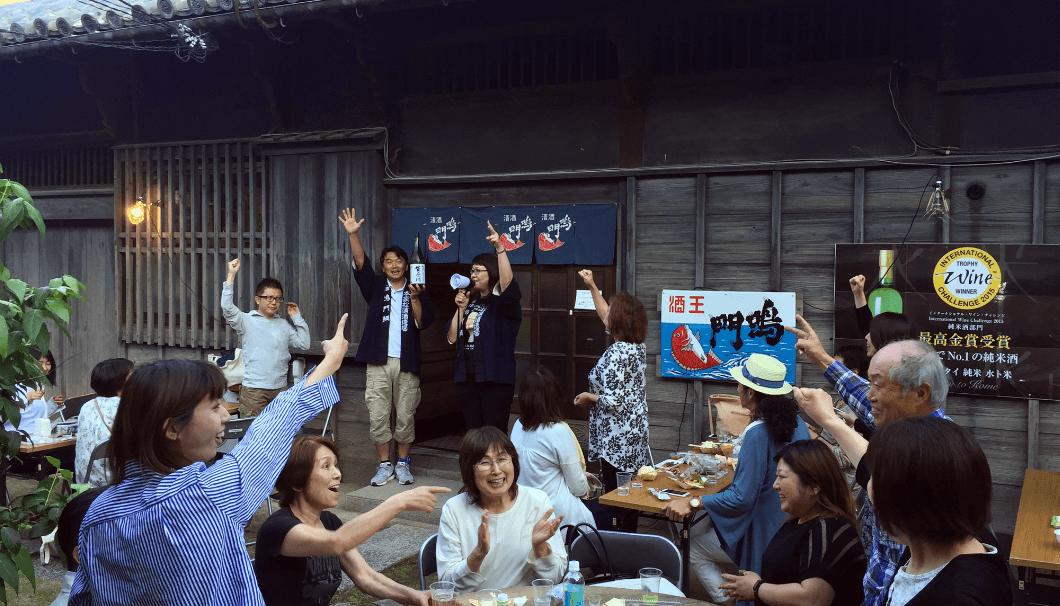 徳島県鳴門市の株式会社本家松浦酒造場で開催される日本酒イベント「ナルトタイ蔵蔵たちきゅう」の様子。蔵の前でお酒を飲んで楽しんでいる写真