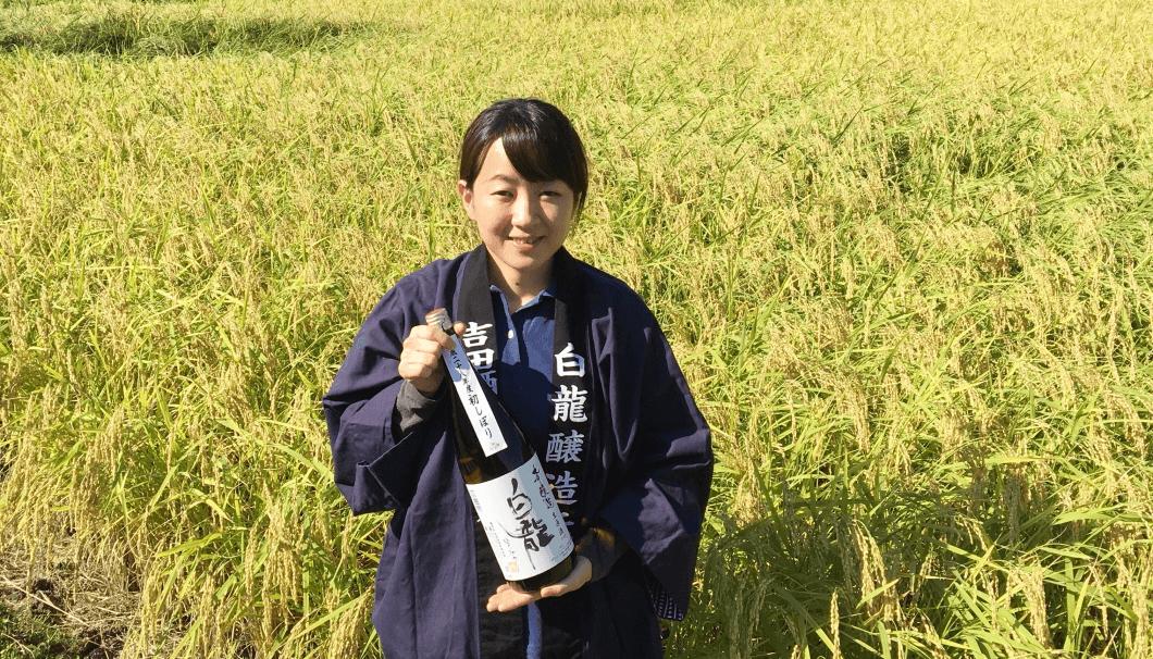 自社田の中で永平寺テロワールのお酒を持つ吉田真子さん