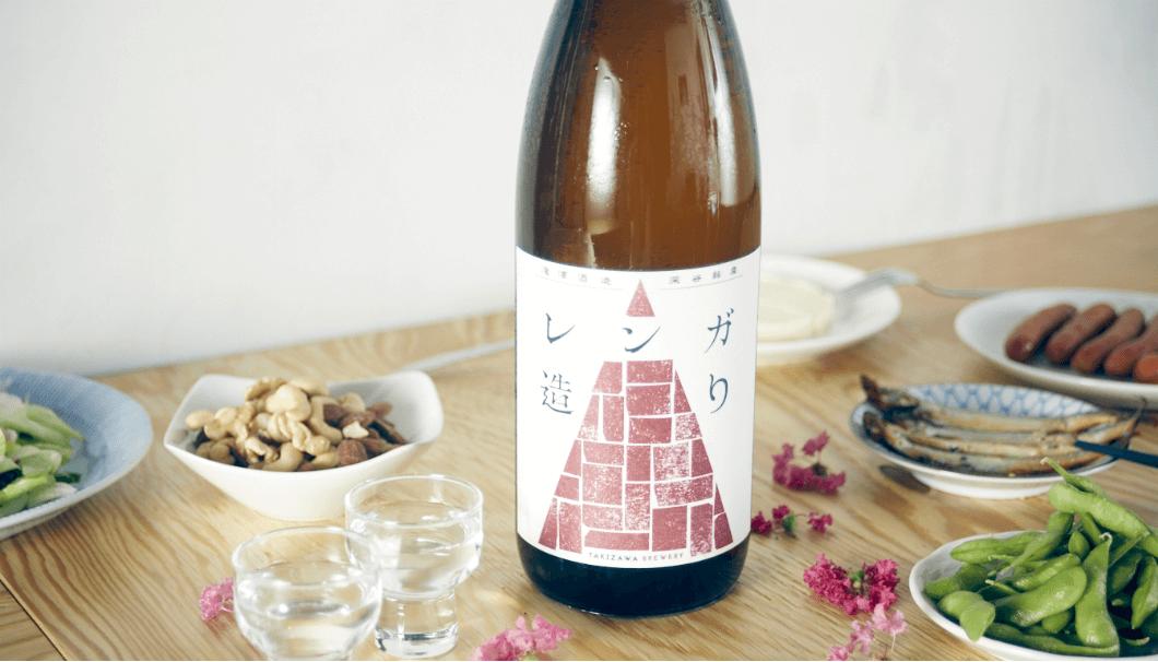 日本酒のオンラインストア「KURAND」と滝澤酒造株式会社(埼玉県深谷市)が共同開発した新ブランドの日本酒「レンガ造り」のボトル、まわりに枝豆などのおつまみがある写真