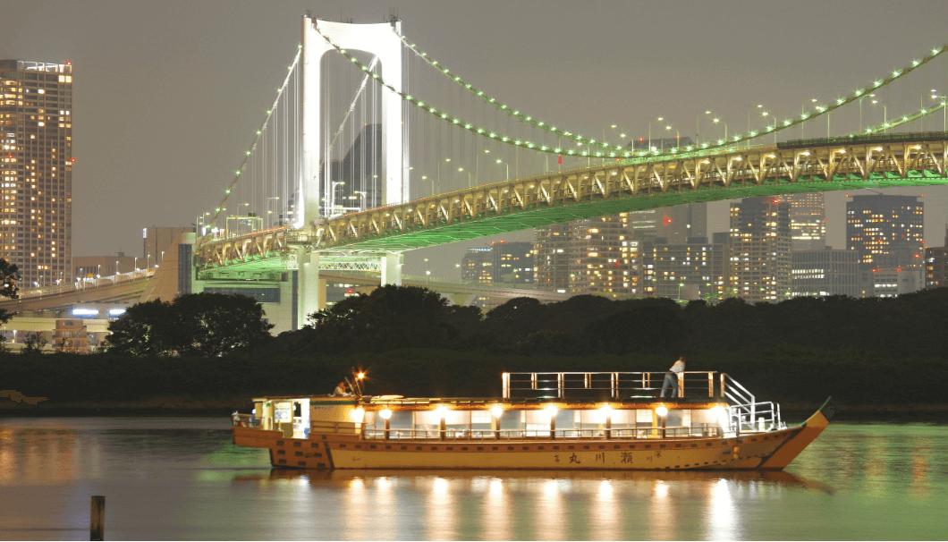 レインボウブリッジを背景に、夜の東京湾に浮かぶ屋形船の写真