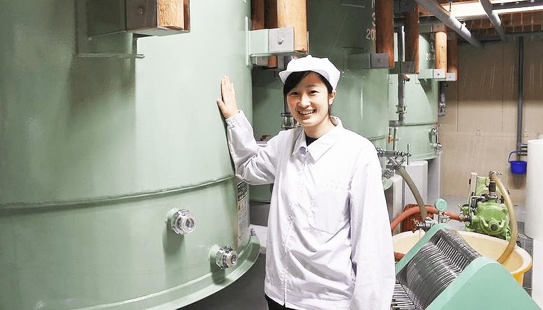 佐仕込みタンクの前に立つ藤酒造店の佐藤麻里子さん