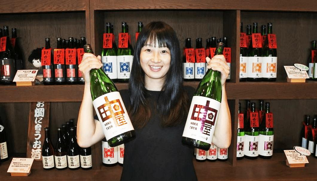 「中田屋」の瓶を掲げる佐藤酒造店の佐藤麻里子さん