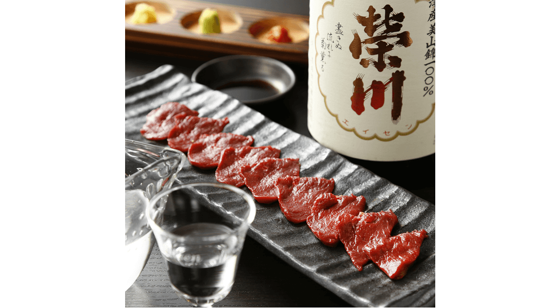 榮川酒造株式会社(福島県耶麻郡)のお酒「榮川」のボトルと、お酒の入ったグラス、馬刺しの写真