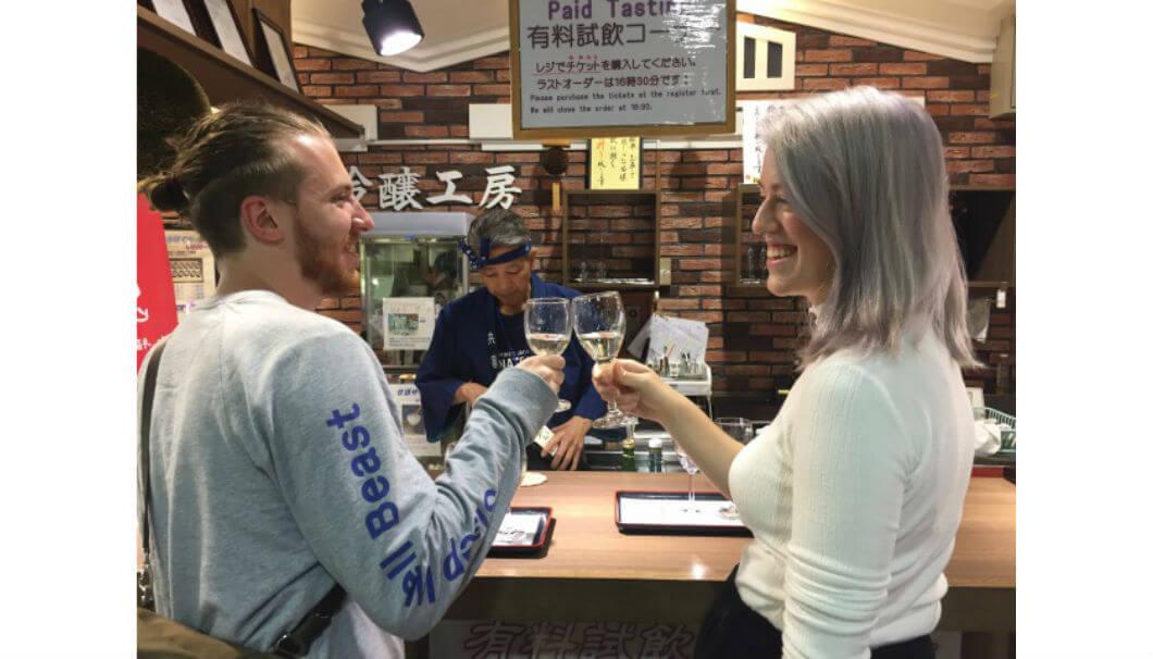 外国人女性と外国人男性がバーカウンターで乾杯している写真