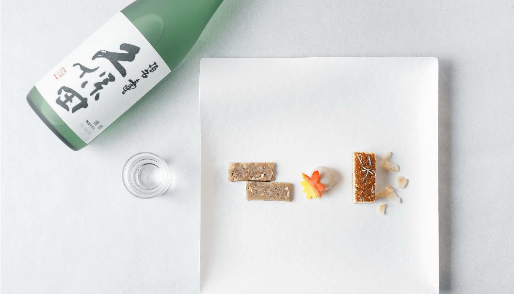 朝日酒造「久保田」のボトルと、お皿に盛られた越乃雪本舗大和屋の和菓子の写真