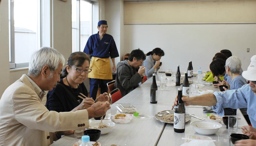 上川町そばうち同好会の指導で打ったそばを試食するツアー参加者