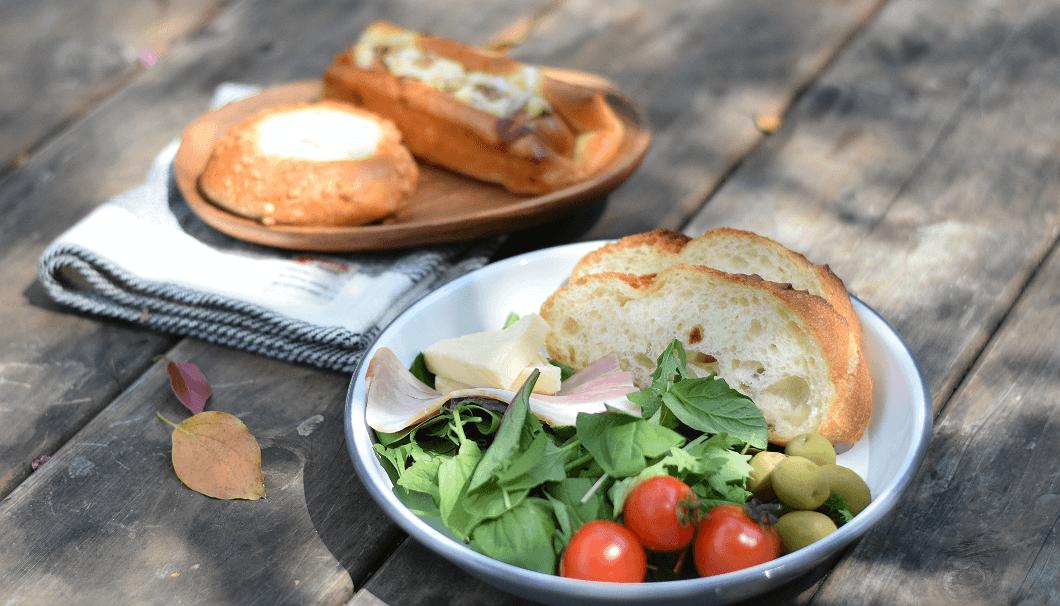 テーブルに並んだ、おしゃれな器に盛ったパンや野菜