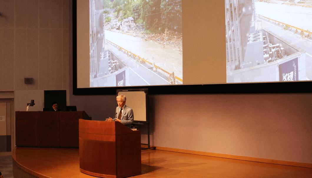 西日本豪雨の被害をバックに話をする桜井博志会長の写真