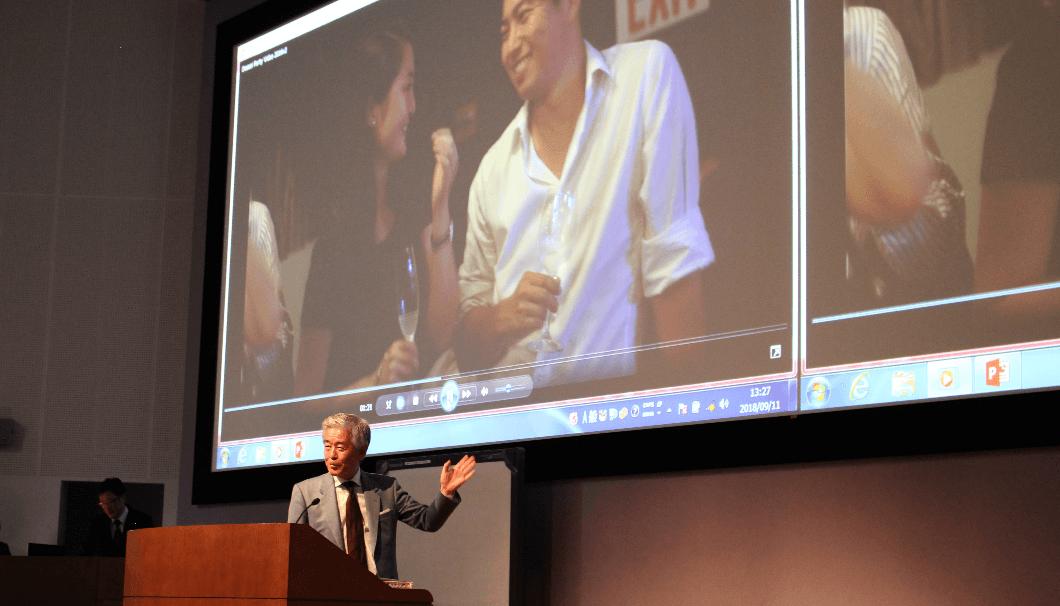 海外で獺祭が楽しまれているスライドをバックに話をする桜井博志会長の