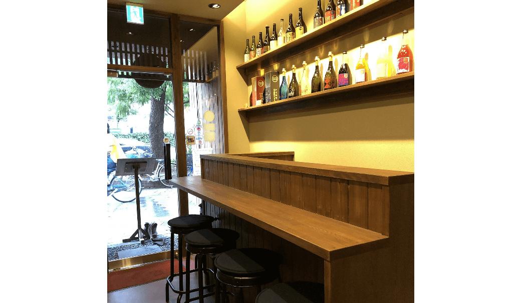 リニューアルされた「NIPPONno SAKE小鼓御里」の店内写真(日本酒柄が並んだ棚と、カウンター)