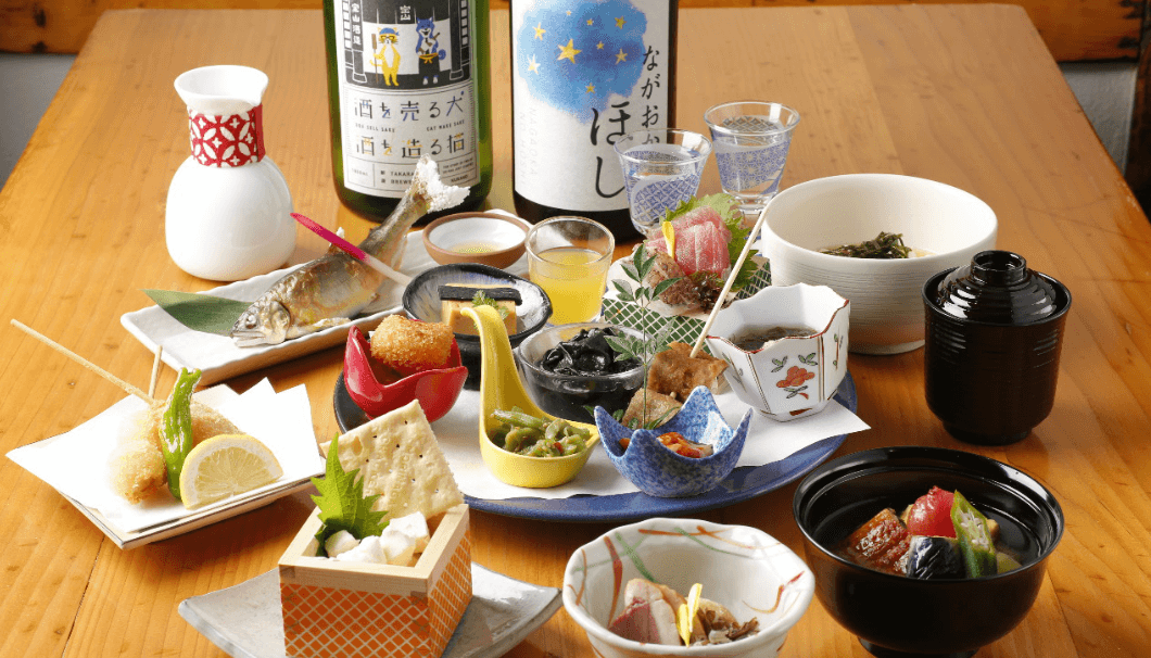小鉢に入ったお料理と、日本酒のボトルがテーブルに並んだ写真
