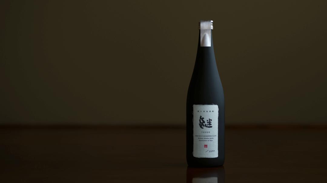 朝日酒造株式会社の新ブランド「継」、黒いボトルが1本立っている写真