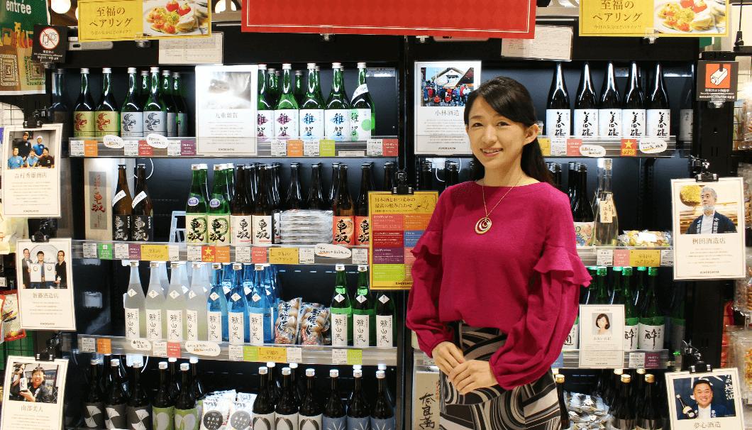 紀ノ国屋アントレ日本橋高島屋S.C店内の日本酒の陳列棚をバックに撮影したあおい有紀さんの画像