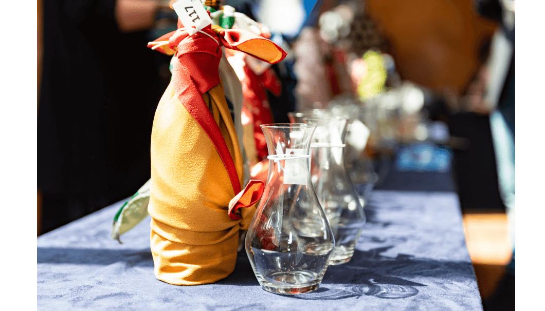 ラッピングをほどこされた日本酒ボトルとグラスが並ぶ写真