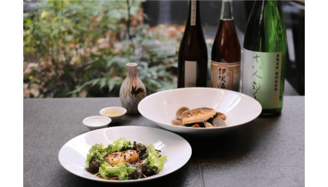 ザ・カフェ by アマン」にて、カジュアルフレンチと燗酒のマリアージュを楽しむ「熱燗ナイト」のイメージ画像。テーブルの上に、日本酒ボトル、とっくり、料理が並んでいる写真