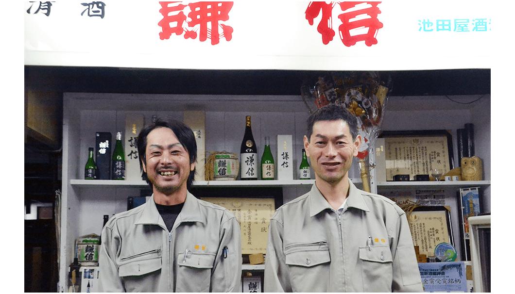 「謙信」の看板の前で笑顔のふたりの男性