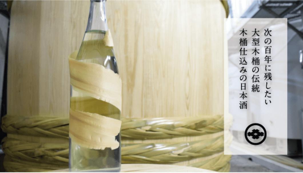 大型木桶と、日本酒のボトルの写真