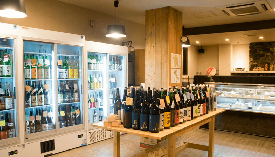 SAKE Fromagerie 香醸の内観写真。日本酒が入った大型冷蔵庫とカウンター