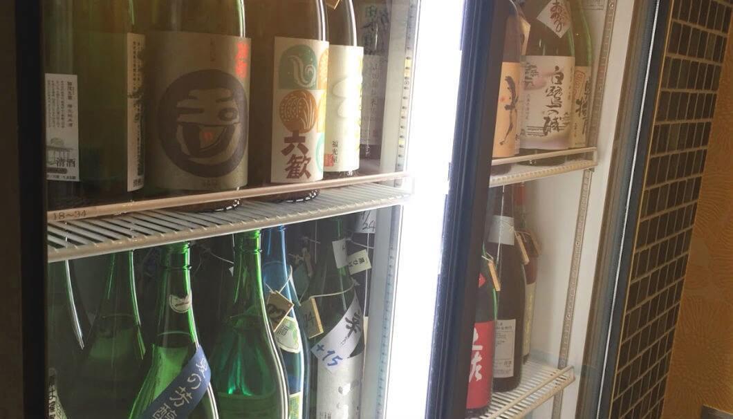 冷蔵ショーケースの中に並ぶお酒の写真