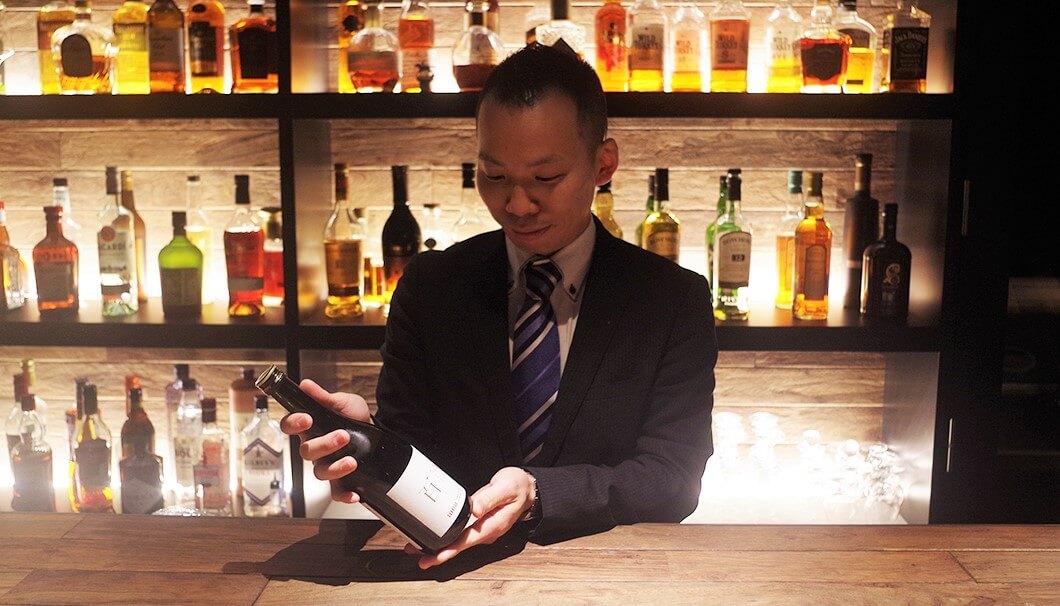 百光のボトルを手に取る瀧田さん。百光を高く評価します。