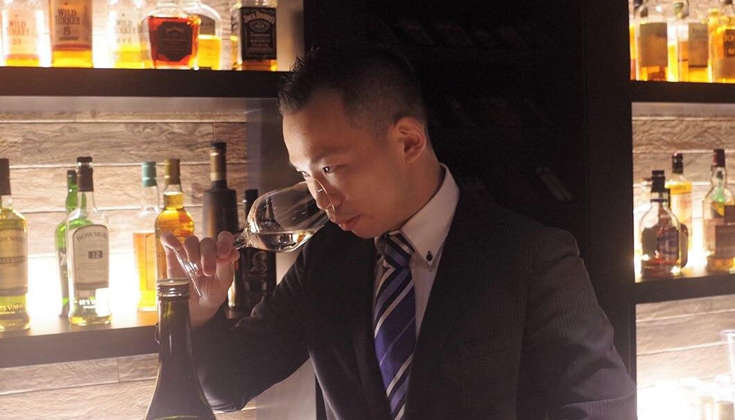 「百光」をテイスティングするソムリエ・瀧田さん。百光を注いだグラスに鼻を近づけ、百光の香りを真剣のな表情で吟味しています。