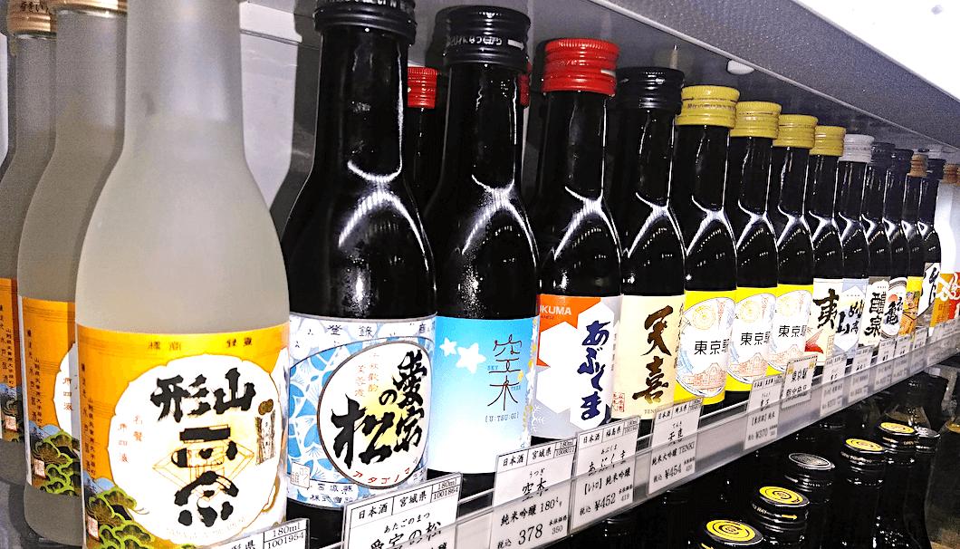 はせがわ酒店 東京駅グランスタ店で小さいサイズの日本酒が並んでいる写真